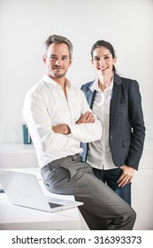 Portrait of two business associates in a luminous office. The man is sitting on the desk with his arms crossed and the woman is standing close to him. They are looking at camera with a little smile