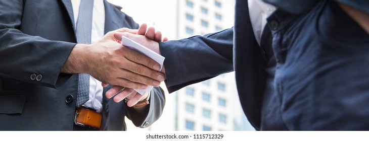 Portrait of two business man shake hand and giving bribe money in white envelope corruption scam. Dishonest cheating in business team illegal black money concept banner