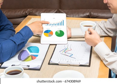 Portrait of two business men drinking coffee and  holding digital tablet in hand and checking analyze data of growing financial chart of sale, revenue and profit in tablet at the cafe coffee shop.