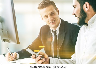 Portrait of two business partners sitting at a table together and working. One is holding his smartphone. The second is writing but can't draw his eyes from the colleague. Toned image