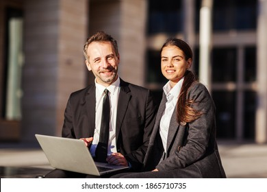 Portrait of two business peope, middle aged man and young woman in suits, smiling at camera while sitting on bench outdoors and discussing project on laptop