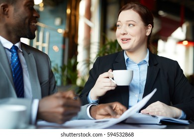 Portrait of two business people during work meeting in modern cafe