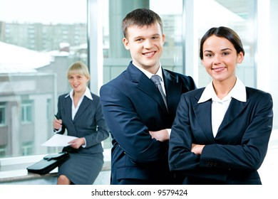 Portrait of two business people folding one's arms in the office