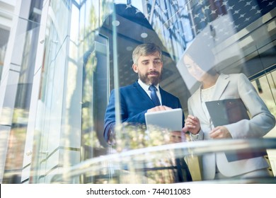 Portrait of two business people, man and woman, using digital tablet discussing work standing behind window in office center, copy space