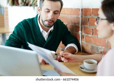 Portrait of two business people, mature man and woman, dressed in smart casual wear working with laptop and documents during meeting in cafe