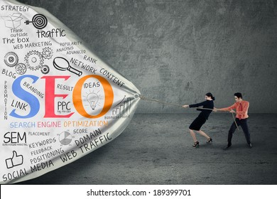 Portrait of two business people pulling SEO banner