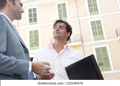 Portrait of two businessmen having a conversation while standing next to a classic building in the city.