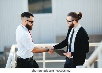 Portrait of two businessmen shaking hands, outside