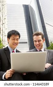 Portrait Of Two Businessmen Working On Laptop Outside Office