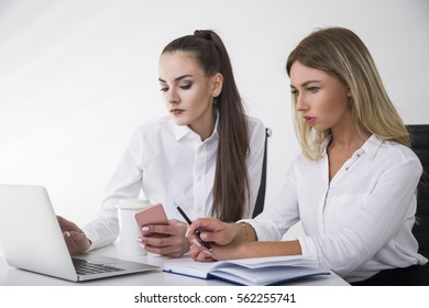 Portrait of two businesswomen at a table in office. One is typing. The second is holding her pen. There is a coffee cup on the desk