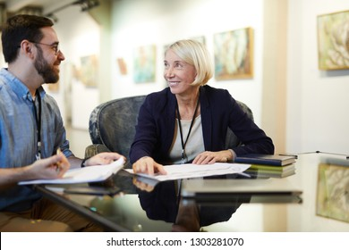 Portrait of two cheerful business people working at desk in modern gallery or museum, copy space