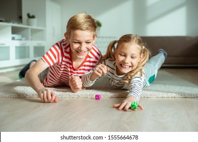 Portrait of two cheerful children laying on the floor and playing emotionally with colorful dices