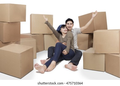 Portrait of two cheerful couple sitting on the floor with cardboards, isolated on white background