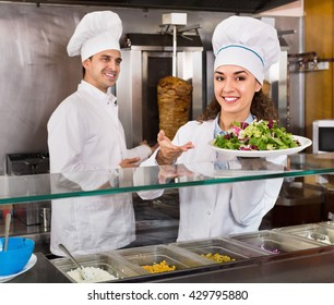 Portrait of two cheerful friendly hospitable chefs with kebab at fast food place