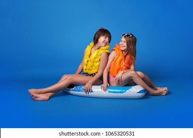 Portrait two cheerful girlfriends in life jacket looking at each other,posing inflatable mattress.Caucasian teenager sisters smile,enjoy vacation,joy,summer season.Isolated blue background,studio.