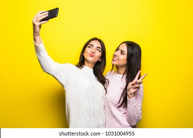Portrait of two cheerful girls dressed in sweaters standing and taking a selfie isolated over yellow