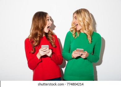 Portrait of two cheerful girls dressed in sweaters holding mobile phones and looking at each other isolated over white background