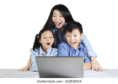 Portrait of two cheerful kids and their mother, looking at a laptop screen and looks shocked. Isolated on white background