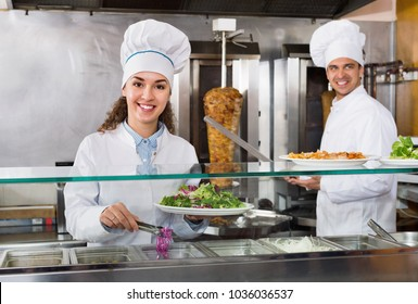 Portrait of two cheerful positive pleasant hospitable chefs with kebab at fastfood place
