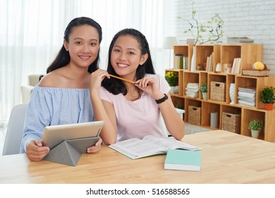 Portrait of two cheerful sisters studying at home