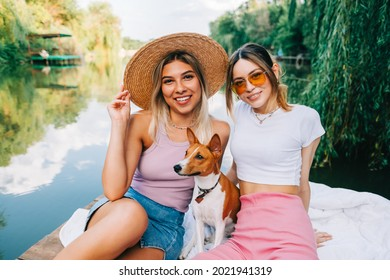 Portrait of two cheerful woman friends resting outdoor on lake pier with dog.