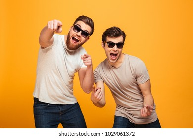 Portrait of a two cheerful young men in sunglasses pointing fingers at camera isolated over yellow background