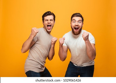 Portrait of a two cheerful young men celebrating isolated over yellow background
