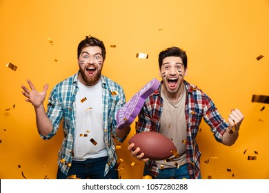 Portrait of a two cheerful young men holding rugby ball and foam glove while celebrating under confetti rain isolated over yellow background