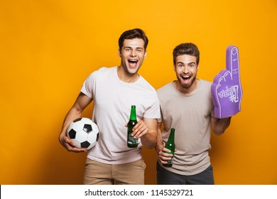 Portrait of a two cheerful young men best friends with soccer ball holding beer bottles and shouting isolated over yellow background