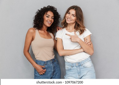 Portrait of two cheerful young women standing together and pointing finger isolated over gray background