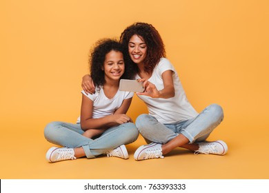 Portrait of a two cheery afro american sisters taking a selfie while sitting isolated over orange background
