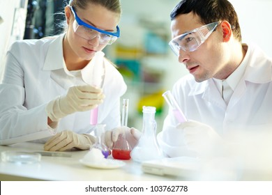Portrait of two chemists holding tubes with pink liquid