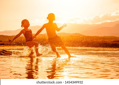 portrait of two children aged 3 and 6 playing in the sea and spraying water around them. Backlight image at sunset