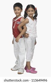 Portrait of two children back to back and hand in hand