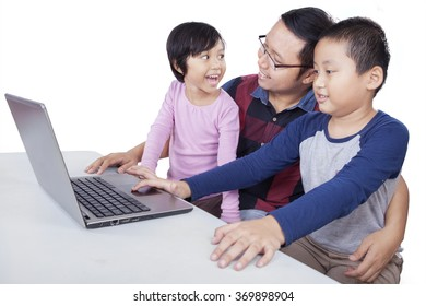 Portrait of two children studying and discussing with their teacher while using laptop on table, isolated on white background