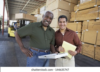 Portrait of two confident workers and man working with forklift in background