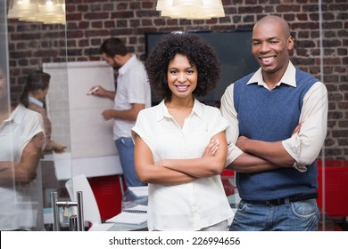 Portrait of two confident young business people with arms crossed in office
