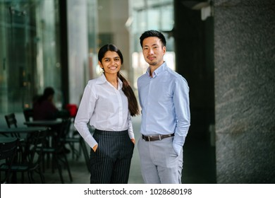 Portrait of two coworkers, team mates or colleagues standing in their office during day. One is an Indian woman, and the other a Chinese man (diverse). They are smiling in a relaxed way.