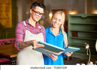 Portrait of two creative young women smiling happily enjoying  work together in art studio choosing pictures for interior design and decor