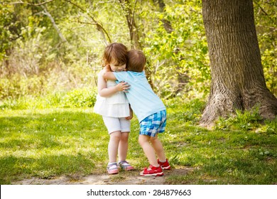 Portrait of two cute adorable baby children toddlers hugging and kissing each other, love friendship in childhood concept, best friends forever