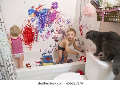 Portrait of two cute adorable white Caucasian little boy and girl toddlers playing painting in bathroom on walls, having fun, lifestyle active childhood concept, early education development