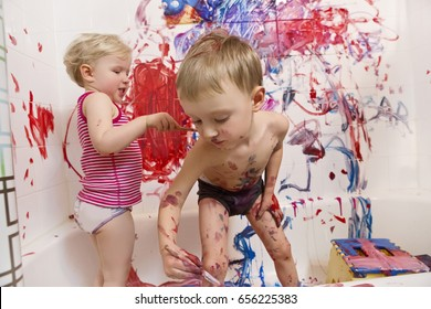 Portrait of two cute adorable white Caucasian little boy and girl playing painting on walls  in bathroom, having fun, lifestyle active childhood concept, early education development