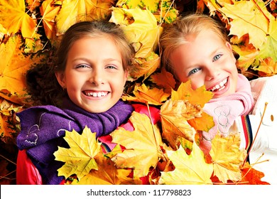 Portrait of two cute girls sisters lying on the leaves at the autumn park.