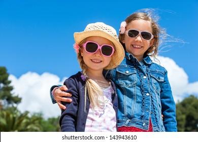 Portrait of two cute kids wearing sunglasses outdoors.