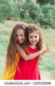 Portrait of Two Cute little girls embracing and laughing at the countryside. Happy kids outdoors