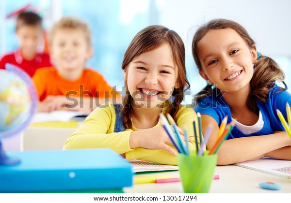 Portrait of two diligent girls looking at camera at workplace with schoolboys on background