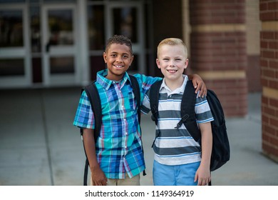 Portrait of Two diverse school kids standing outside their elementary school building. Back to school photo of diverse school kids wearing backpacks