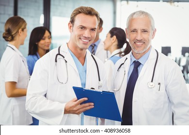 Portrait of two doctors with clipboard in hospital and colleagues standing behind and discussing