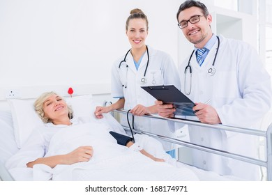 Portrait of two doctors visiting a female patient in the hospital