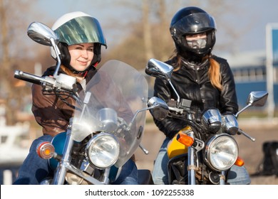 Portrait of two European pretty female bikers with classic and street style bikes in city